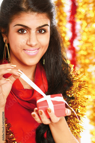 Beautiful girl with gift christmas decorated background.