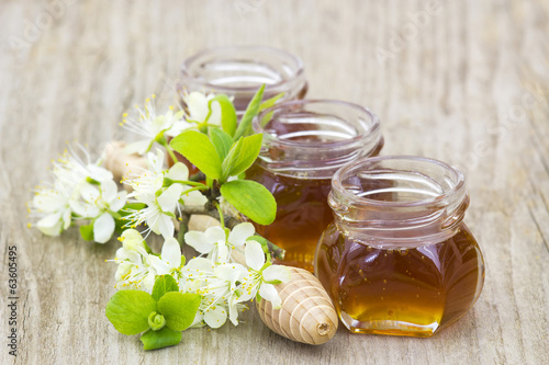 Honey, flowers and honey dipper on wooden background