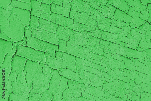 Painted green wall with cracks.