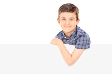 Young boy posing behind blank panel