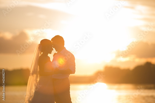 Newly married couple on the river with sunset