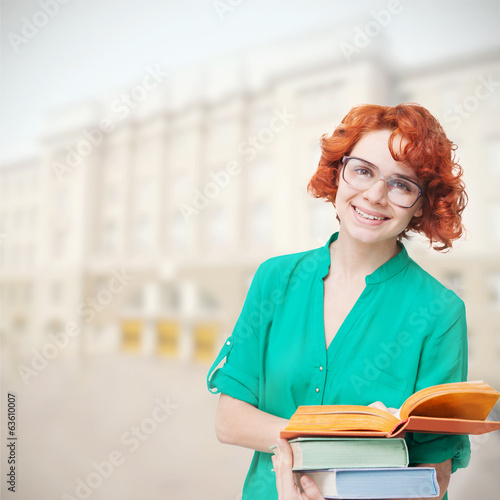 red-haired girl in glasses with books