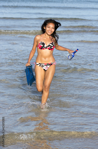 Girl with diving equipment running from the sea