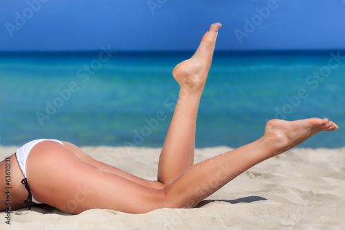 canvas print picture Woman is lying on the beach