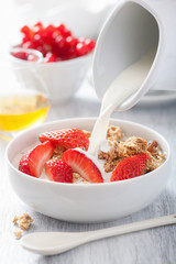 milk pouring over granola with strawberry for breakfast