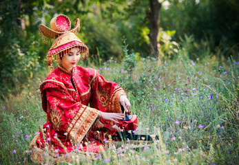 Girl in Chinese princess costume sits on grass and drinking tea