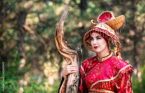 Girl in Chinese princess costume in the pine forest
