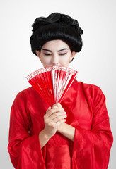 Asian style portrait of a woman in red kimono with a fan