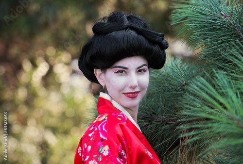 Asian style portrait of a woman in red kimono in pine forest