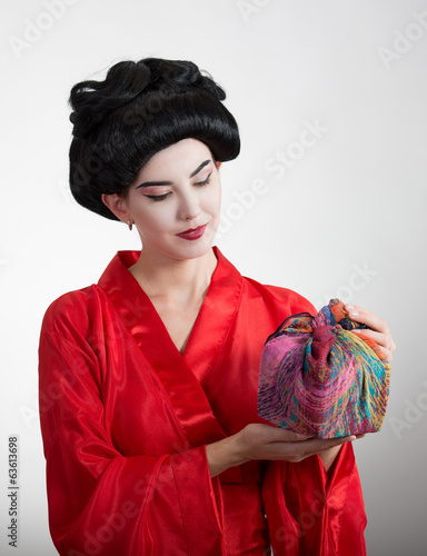Asian style portrait of a girl in red kimono with a wrapped box