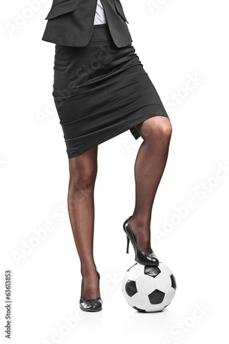Businesswoman with football under her foot