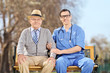 Doctor and an elderly gentleman sitting in park