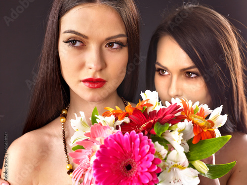 Two sexy lesbian women with flower.
