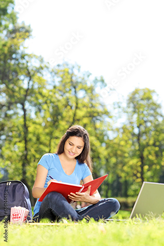 Female student writing in a notebook outdoors