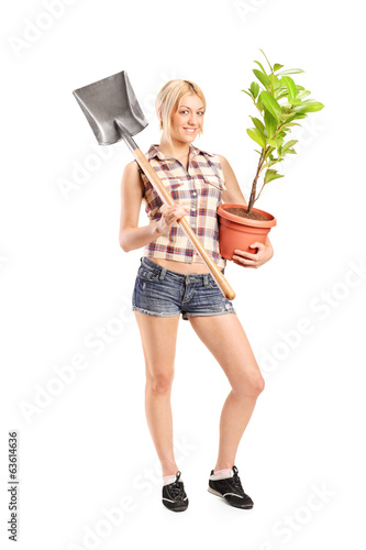 Wоman holding shovel and a plant