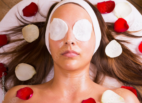 Caucasian woman get massage in a spa bed with flower.