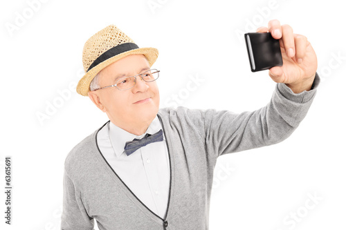 Senior gentleman taking a selfie with cell phone