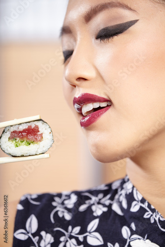 beautiful asian woman eating sushi with chopsticks