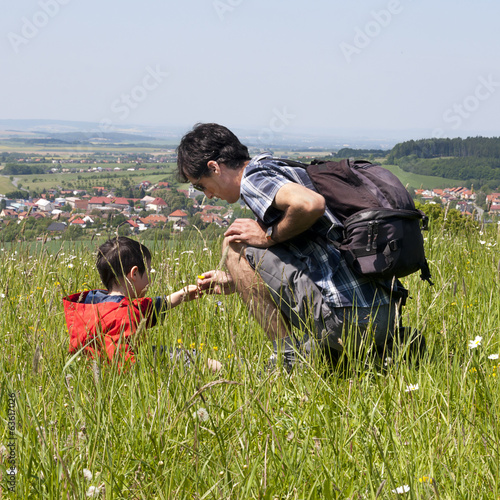 Father and son in nature on a countryside meadow in summer.