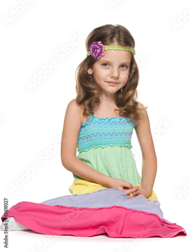 Little girl sits on the white background