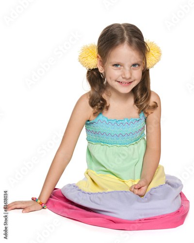 Smiling little girl sits on the floor