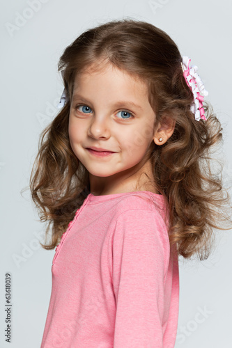 Smiling little girl against the gray background