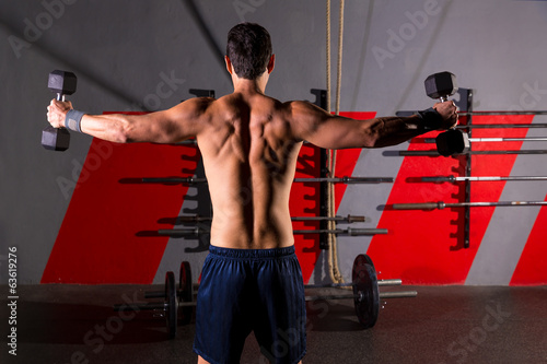 hex dumbbells man workout rear view at gym