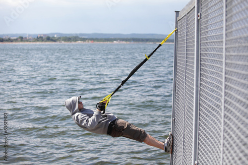 hooded man outdoor,suspension training at the sea
