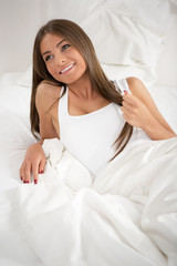 Cute young woman resting in the bed
