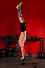 kettlebell handstand man workout in red gym