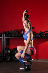 kettlebell lifting woman workout in red gym