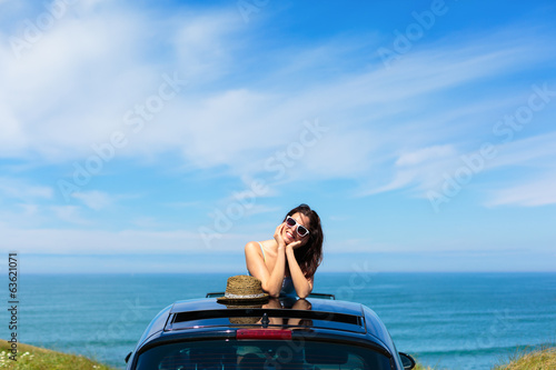 Woman on summer travel leaning out sunroof