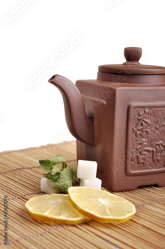 earthenware teapot and lemon with mint and sugar