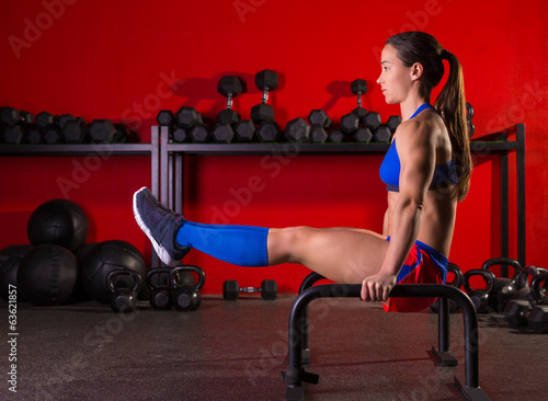 Parallettes woman parallel bars workout at gym
