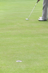 Golfer on putting green.