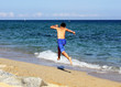 Boy running on the sea beach on summer holidays