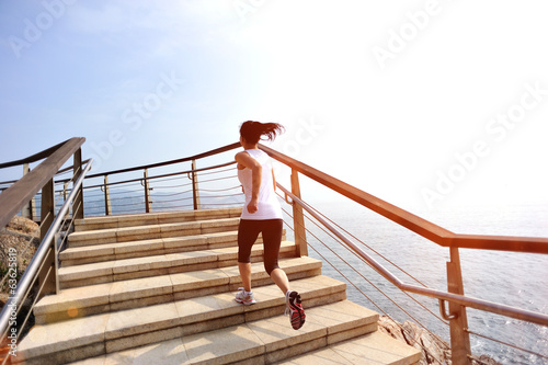 healthy lifestyle sports woman running on seaside stone stairs