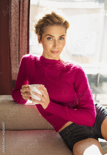 Beautiful blond woman sitting on coach in home and holding a cup