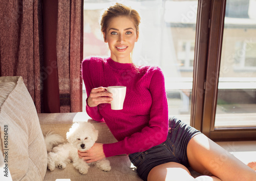 Happy woman sititing with puppy on coach and drinking a tea