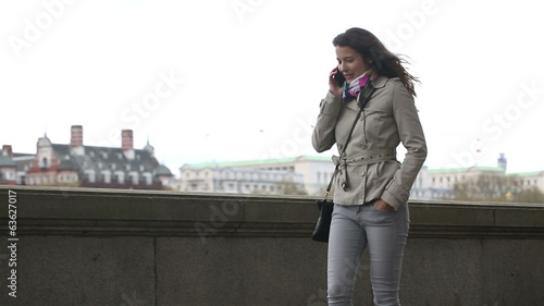 Attractive woman walking and talking on her phone in London