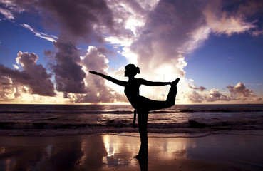 Yoga woman on the beautiful beach at sunrise
