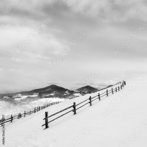 Black fence on white snow on mountains - 63627697