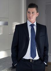junger Mann im Anzug steht da und lächelt