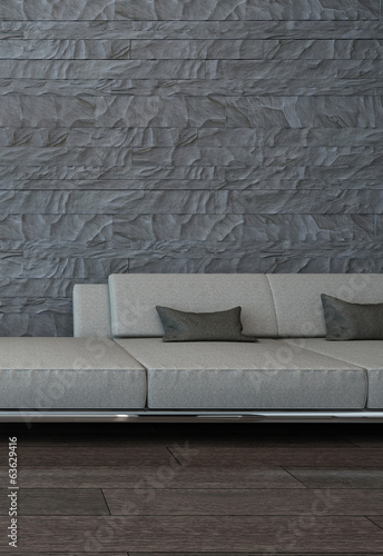 Gray couch against stone wall