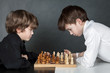 Two serious boy playing chess, studio
