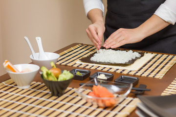 Woman chef filling japanese sushi rolls with rice