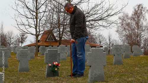 Man with walking  stick  near soldier's grave