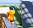Orange cocktail on beach table