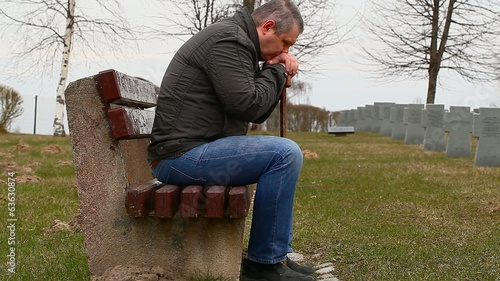 Man with walking stick on bench in the cemetery