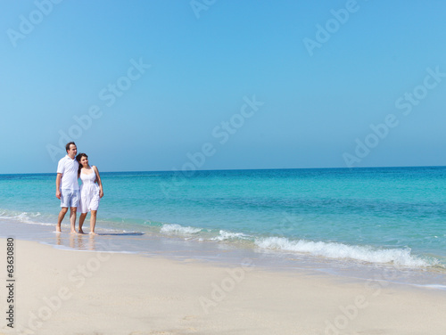 Young happy couple walking on the beach